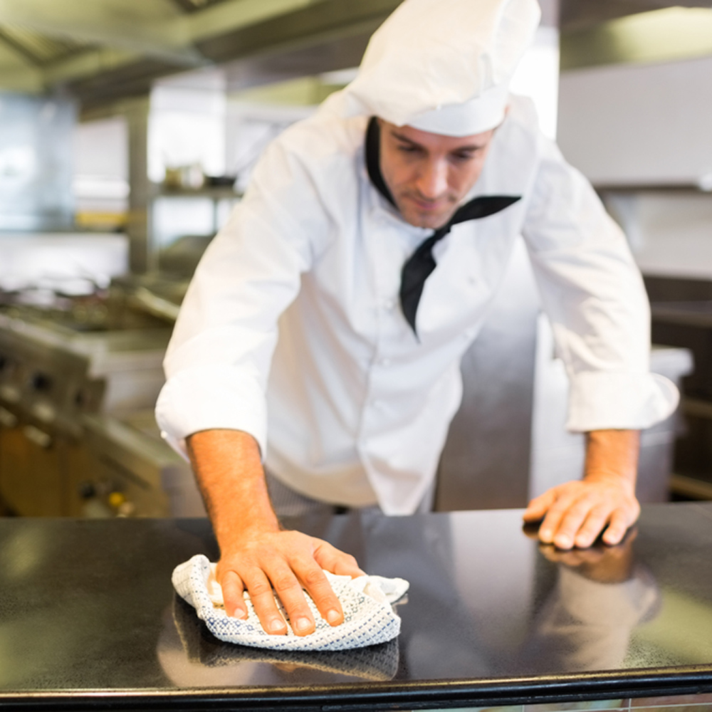 Food service worker cleaning with a Dempsey Uniform linen kitchen towel
