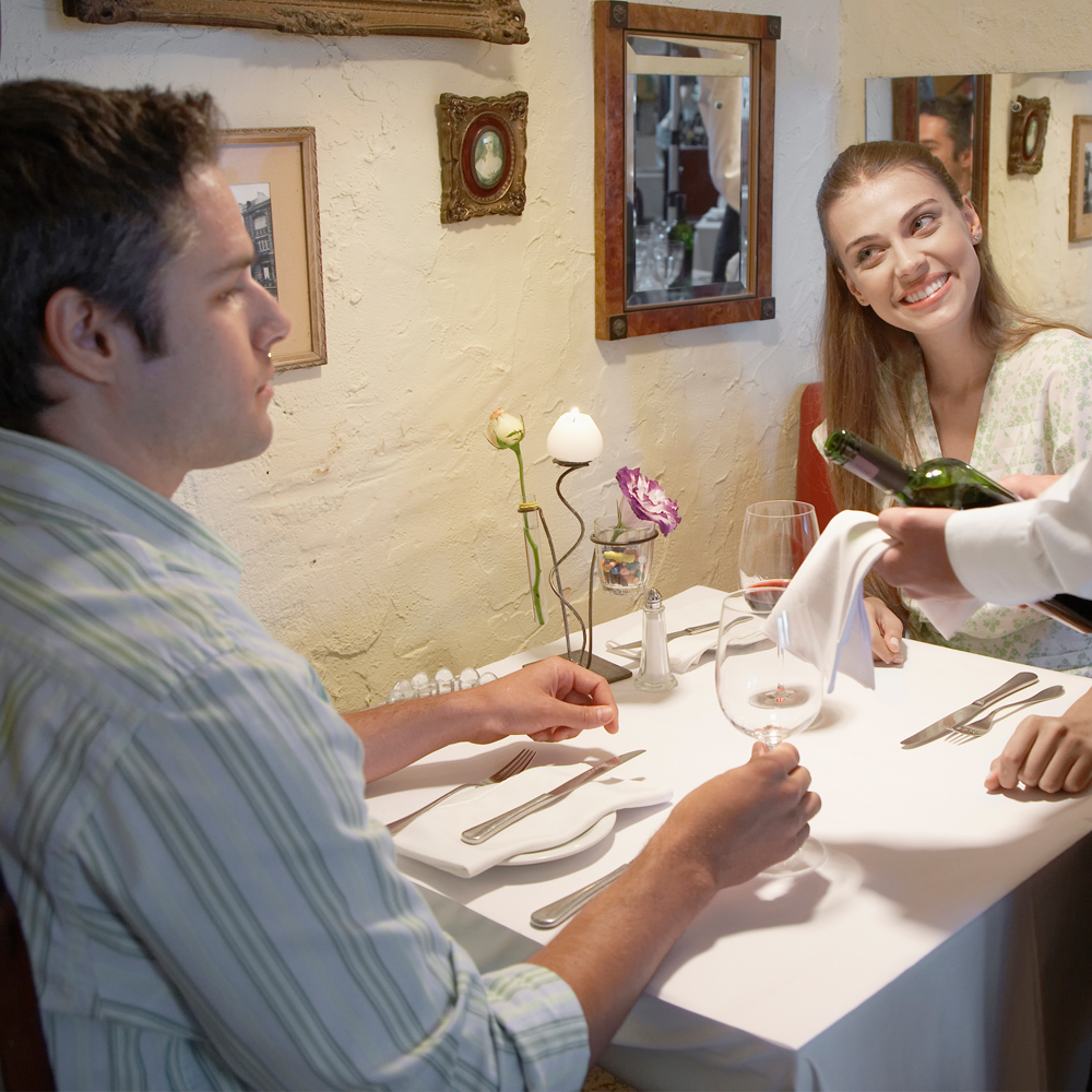 Couple dining at a table set with a Dempsey Uniform linen tablecloth